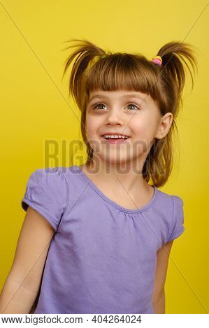 Portrait Of Smiling Little Caucasian Girl With Pigtails And Bruise Under The Eye And Looks Away. Ver