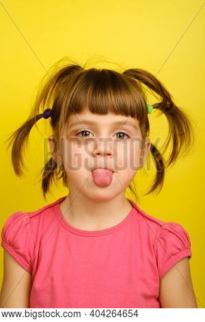 Close-up Of Funny Little Girl With Bruised Eye Showing Her Tongue, Looking At Camera On Yellow Backg