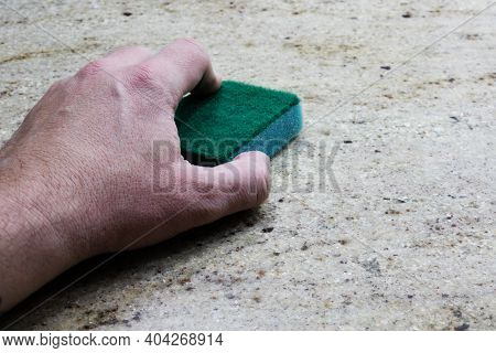 A Man Cleans Up A Granite Countertop With A Sponge