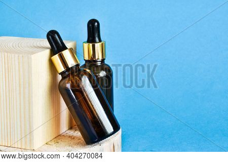 Glass Cosmetic Bottles With Pipettes On A Wooden Cube On Blue Background. Anti-aging Formula, Liquid