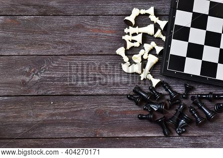 Chess Board And Chess Figures On Wooden Background. Flat Lay, Copy Space. Black And White Chess Figu