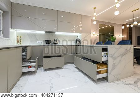 Open drawers at well designed large modern white wood and marble kitchen united with living room as a pert of studio flat