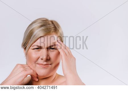 A Blonde Senior Woman With A Frown Looks At The Displeased Wrinkles On Her Face. White Background. A
