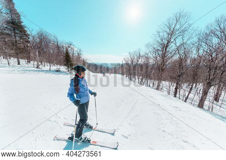 Skier woman taking a break during skiing on slope. Happy Asian active woman relaxing on sunny day at ski resort. Winter sport holiday.