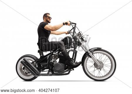 Full length profile shot of a man with sunglasses and leathe pants riding a black chopper motorbike isolated on white background