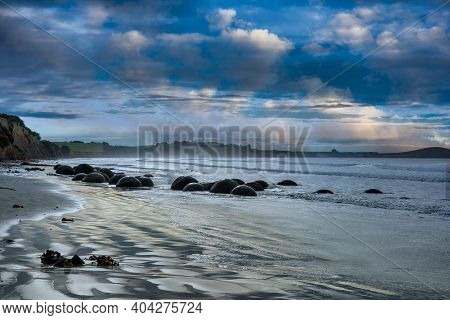 Dramatic Moody Blue Cloudscape Reflecting Blue Tones On The Dunedin Beach And Its Iconic Boulder For