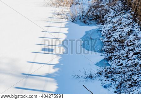 Shadow Of Wooden Fence Posts On White Surface Of Frozen Lake Near Shoreline.