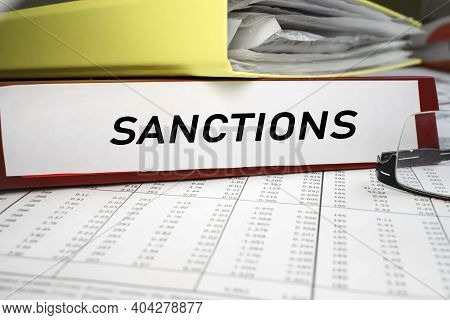 The Word Sanctions Is Written On The Red Folder That Lies On The Business Documents. Economic And Po