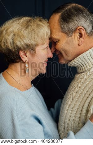 Close Up Portrait Of Old Couple Wife And Husband Smiling. Dark Blue Background. Happy Lovers On Reti