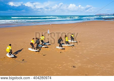 Vale Figueiras, Portugal - January 2, 2021: Surfers getting surflessons at Vale Figueiras beach in Portugal