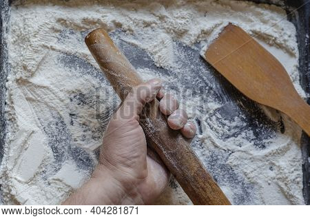 Hand, Wooden Rolling Pin, Spatula And Wheat Flour. The Man's Hand Holds The Rolling Pin Over The Sur