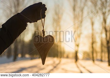 Womans Hand Holding A Wooden Heart On Winter Snowy Forest Evening Blurred Background. Love Winter Or