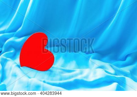 Close-up And Selective Focus Of One Red Heart On Blue Fabric Satin Soft Background. Concept Of Roman