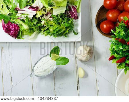 Garlic Sauce In A Gravy Boat On The Table. Cooking A Dietary Dinner. Salad Ingredients.