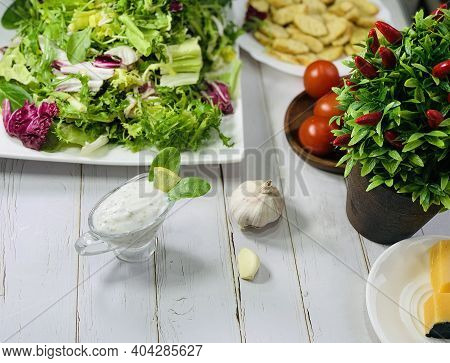 Tartar Sauce In A Gravy Boat On The Table. Preparing A Diet Breakfast. Tomatoes And Lettuce In A Pla