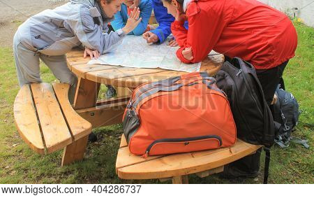 Bessagan, Norway - July 2018 A Group Of Young People Bent Over A Paper Map. The Finger Of The Hand P