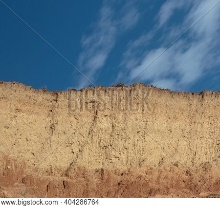 A Vertical, Natural Earthen Wall. A Streak Of Blue Sky Turns Into Yellow And Brown Clay Streaks. Soi
