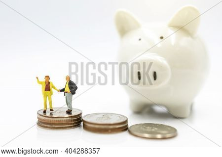 Miniature People: Elderly Person Standing On Coins Stack With Piggy Bank, Retirement Planning Concep