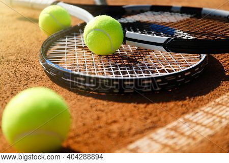 Tennis Balls And Rackets On Clay Court, Closeup