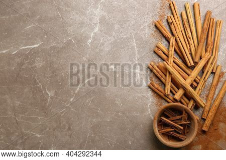 Aromatic Cinnamon Sticks On Grey Table, Flat Lay. Space For Text