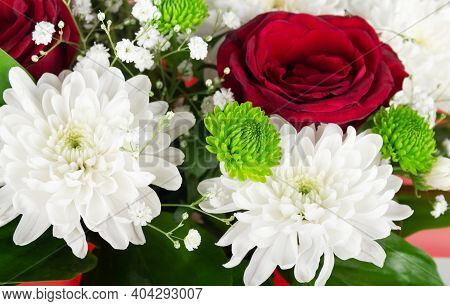 Bright Bouquet Of Spring Flowers, Chrysanthemums And Scarlet Roses On A Background Of Green Leaves
