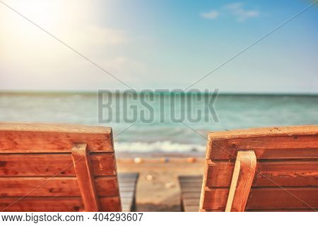 Two Wooden Latticed Sun Beds. Beach At A Boarding House Or Hotel. Sunbeds On The Beach. Clear Sea Su