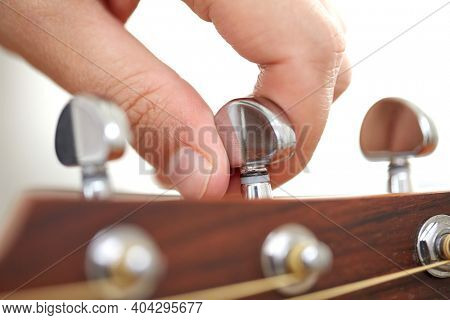 music and musical instruments concept - close up of hand tuning guitar strings with pegs