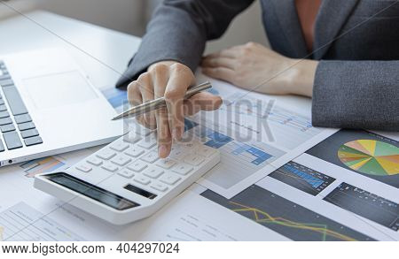 Financial businesswoman calculating corporate income tax data And analyzing charts of financial stoc