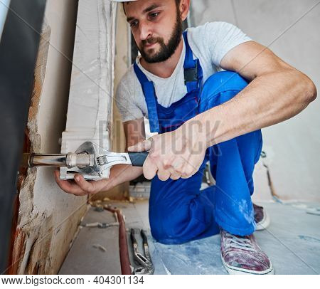 Bearded Young Man In Work Overalls Using Plumber Wrench While Installing Heating Radiator In Room. M