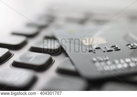 Bank Plastic Card Lying On Calculator Closeup. Payment Of Taxes Concept