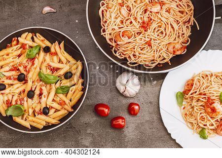 Traditional Italian Food. Pasta With Tomato Sauce, Basil, Parmesan, Olives. Food In A Pan And On A P