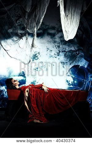 Bloodthirsty vampire woman lies in a coffin in the night cemetery.