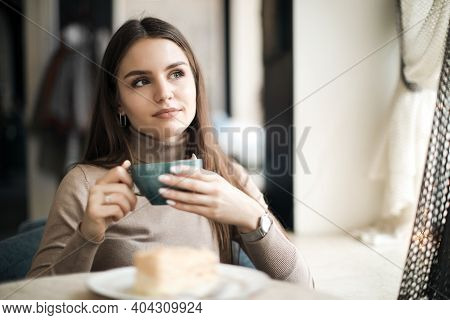 Beautiful Young Cheerful Woman With Long Hair Is Sitting And Drinking Coffee Or Tea. Close-up Of A P