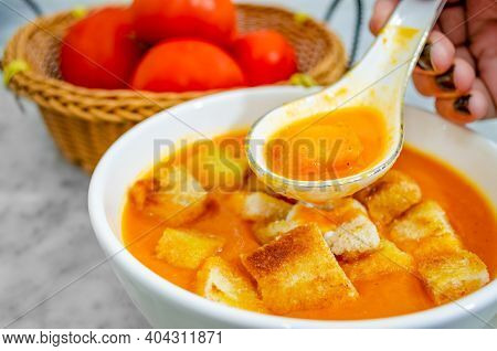 Closeup Of Human Hand Taking Tomato Soup With Bread Croutons In A Soup Spoon