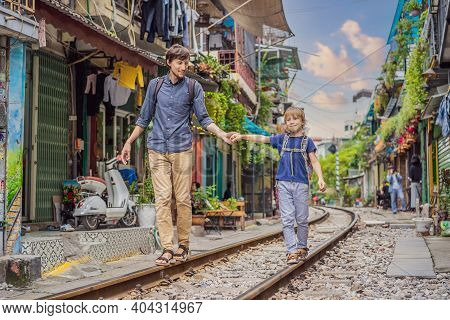 Father And Son Travelers Walk Around Railway Paths Which Go Through Residential Area In Hanoi City.