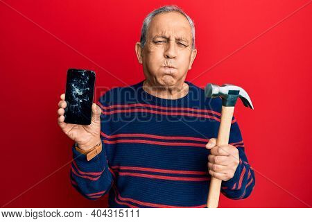 Senior hispanic man holding broken smartphone showing cracked screen and hammer puffing cheeks with funny face. mouth inflated with air, catching air.