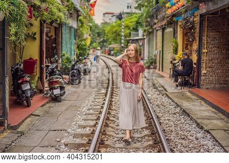 Woman Is Walking Of Hanoi City Railway. Perspective View Running Along Narrow Street With Houses In