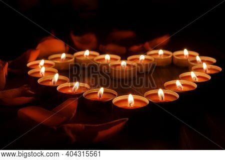 Red Candles Are Arranged In The Shape Of A Heart On A Dark Background. There Are Rose Petals All Aro