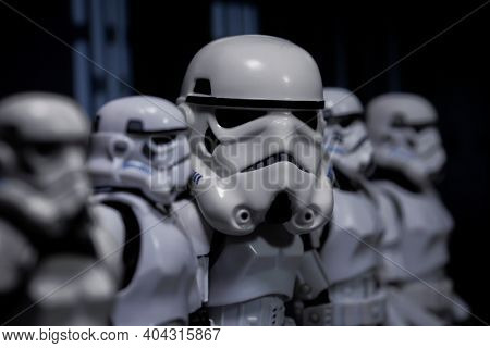 JAN 20 2021:  humorous concept of Star Wars Stormtrooper with oversized helmet  standing in line with normal size troopers - Hasbro action figure