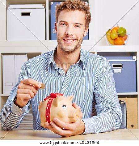 Smiling young man saving his Euro money in a piggy bank
