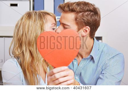 Young couple hiding behind a red heart for a romantic kiss