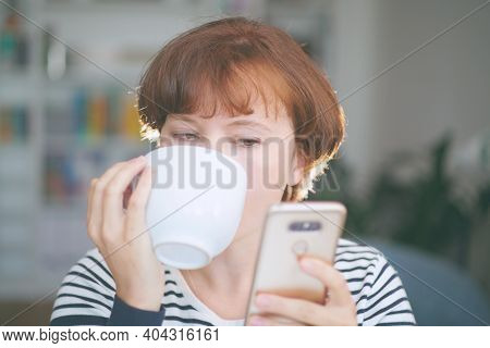 Young Beautiful Woman Drinking Coffee And Looking At Smartphone. Woman Happy Girl With Cellphone. Ho