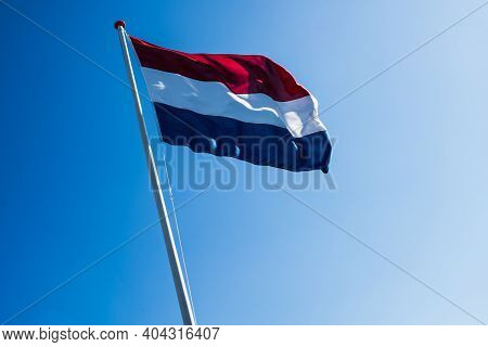 Free Waving Flag Of Holland Against The Blue Sunny Sky. Liberation Day In Netherlands.