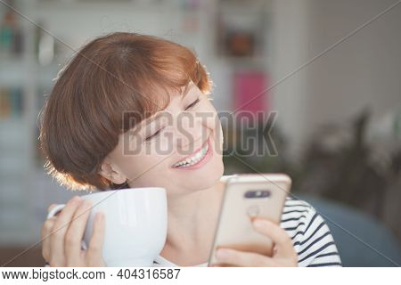 Young Beautiful Woman Holding Coffee Cup, Looking At Smartphone And Smiling. Woman Happy Girl With C