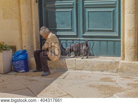 Lecce, Italy April 4, 2018 Senior Italian Woman With Dog On The Sidewalk. Scene Of Elderly People Da