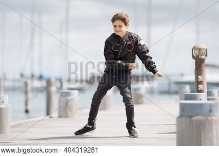 Dancing Boy On The Beach With Yachts In The Background. Family Vacation By The Sea. Active Lifestyle