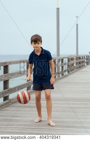 Boy On The Beach With Ball. Family Vacation By The Sea. Active Lifestyle