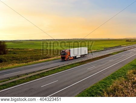 Truck With Semi-trailer Driving Along Highway On The Sunset Background. Goods Delivery By Roads. Ser