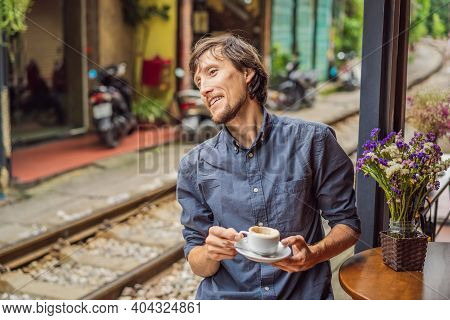 Young Man Traveler Drinks Vietnamese Coffee With Egg Sitting By The Railway Paths Which Go Through R