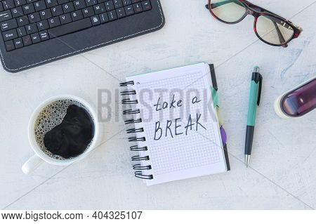 Take A Break. Concept Time Off. Words Take A Break In Notebook On The Working Table With Cup Of Coff